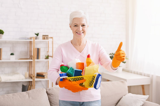 Smiling mature housewife cleaning floor at home