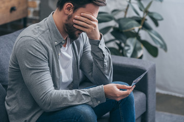 sad man sitting on couch, holding photo and crying at home, grieving disorder concept