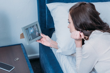 upset woman lying in bed and looking at frame with picture of man at home