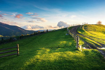 beautiful countryside scenery in mountains. fence on the grassy field. country road uphill the knoll. wonderful springtime weather at sunset with reddish clouds
