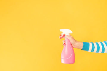 Home cleaning chores. Woman hand armed with atomizer. Copy space on yellow background. Wall mural