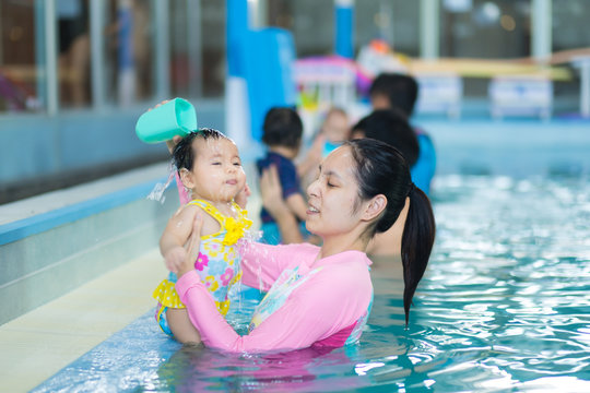 Mother pouring water on baby head  to teach her baby. early development class for infants swimming. Baby swimming concept. Mother and baby swim in the pool.