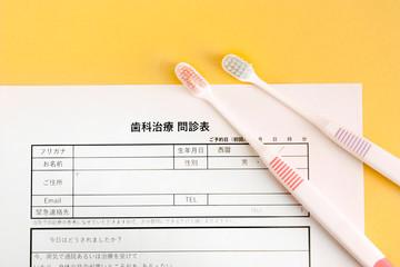 歯の治療の問診票と歯ブラシ、歯医者の予約