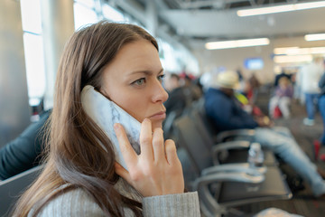 Woman waiting at airport calling on cell phone
