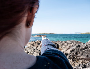 Over the shoulder shot of one woman pointing to a small island in the distance on a sunny day, with earrings and sunglasses. Taken on Renvyle beach along the Wild Atlantic Way in Ireland.
