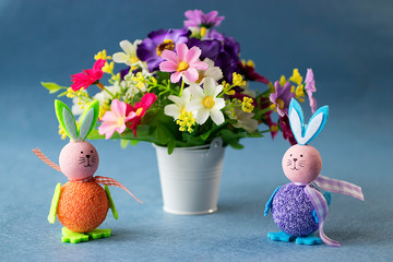 Two decorative rabbits and bright flowers on a gray background. Easter concept.
