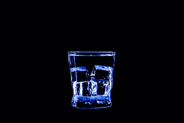 Ice cube in a glass of blue water or drink. Light, refreshment.
