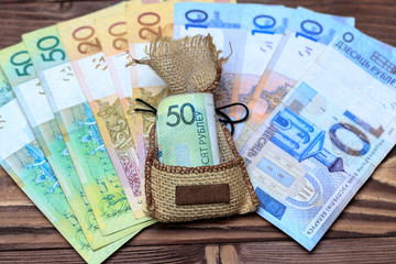 wooden background. on it laid out Belarusian money. In the center in the bag 50 rubles