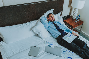 Tired businessman sleeping with documents by his side