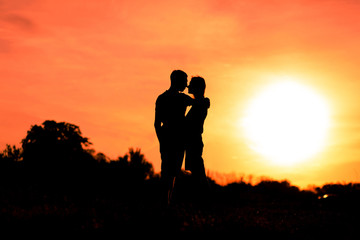Young man hugging his girlfriend on a sunset sky background