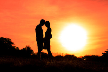 Girl and boy are hugging on a sunset sky background