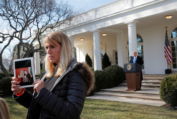 """Angel mom"" Wolff displays photo as U.S. President Trump declares national emergency at the southern border at the White House in Washington"