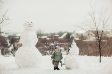 Kid in the winter in the snow. Big snowmen. Walking in the park