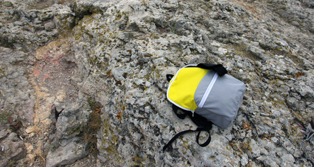 bright yellow small backpack on top of gray rocky cliff background closeup