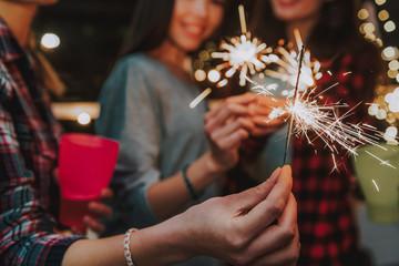 Burning sparklers in female hands at celebration