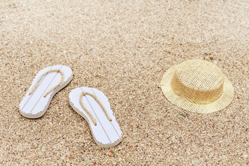 Beach flip-flops and hat on sandy beach. Beach accessories. Copy space.