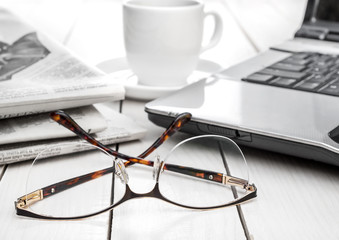 Eyeglasses with newspaper, laptop and cup of coffee on the white table.