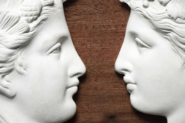 sculpture of two faces looking at each other made of plaster
