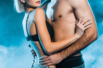 cropped view of seductive couple hugging on blue smoky background