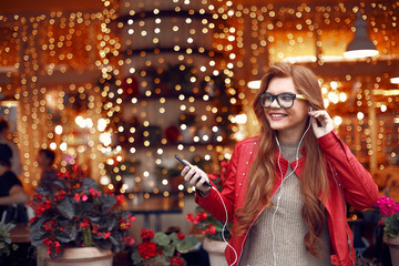Charming red-haired girl holding cellphone and listening music