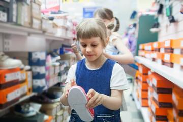 Girl   choosing summer shoes in   store.