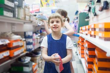 girl choosing  shoes   in   store.