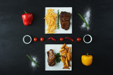The concept of artistic paintings from vegetables. Delicious grilled steak with vegetables tomatoes and fries