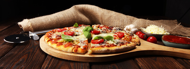 Vegetarian Italian pizza with melted cheese, red tomatoes and green basil on a table decorated by cheese, tomato and cherry tomatoes Fotomurales