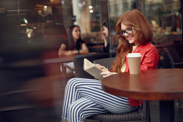 Charming red-haired lady reading book and smiling