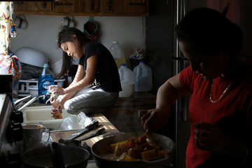 Carolina a migrant from Honduras, cooks food as her sister Rachel washes a doll in Texico