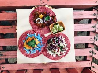 Red tortillas with colorful vegan fillings