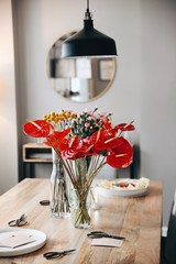 Vases with colorful flowers on a dining table