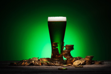 glass of irish beer standing on wooden table near golden coins on green background