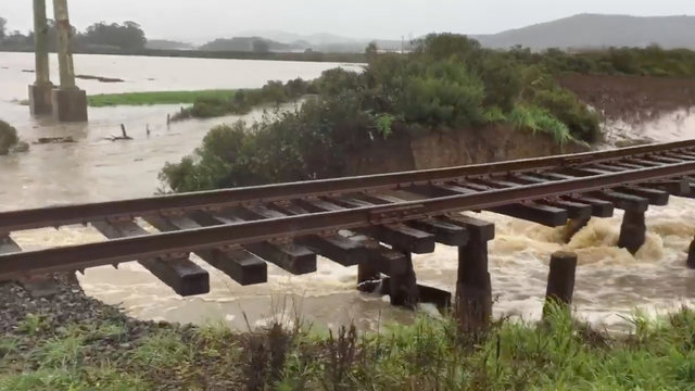 Floodwater rushes past washed out railroad tracks in Novato Creek