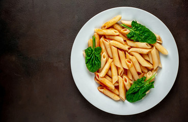 Penne pasta in tomato sauce on concrete background