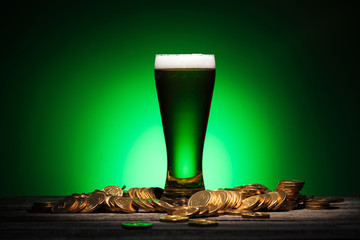 glass of green irish beer standing on wooden table near coins on green background