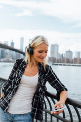 USA, New York City, Brooklyn, smiling young woman standing at the waterfront with headphones and cell phone