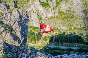 Man swinging in a hammock set up high in the air, between two mountain ridges, taking a break during a via ferrata route - summer activity in Baia de Fier, Gorj county, Romania