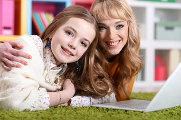 Portrait of young woman with girl using laptop