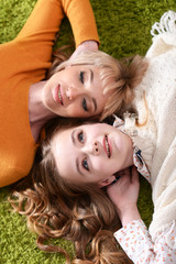 Portrait of mother with daughter lying on green carpet