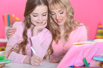 Portrait of girl reading book with mother