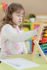 Portrait of little girl counting on abacus