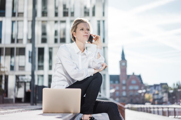 Young businesswman with laptop, sitting on stairs, talking on the phone