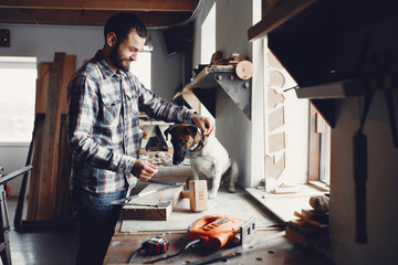 A man carves a tree. The carpenter works in a studio. Boy with cute dog