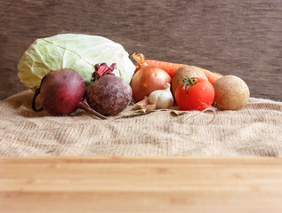Raw vegetables for beet soup borsch. White cabbage, beet, carrot, potato, tomato, garlic on a wooden board