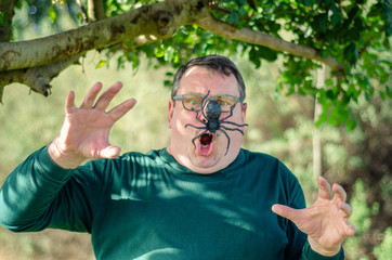 Man yells when he meets a big spider spider coming down from a tree in the grove