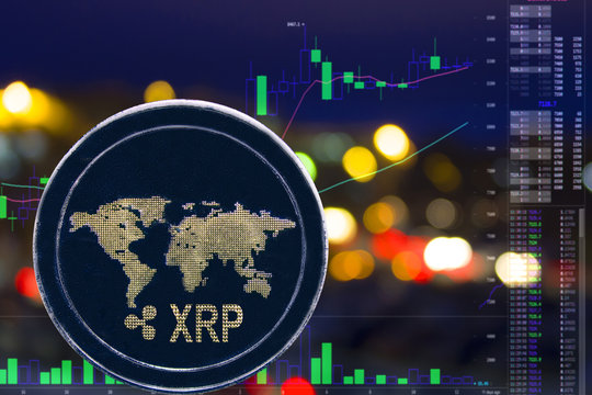 Coin cryptocurrency XRP on night city background and chart.