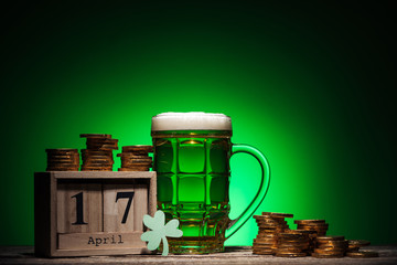 glass of green irish beer near golden coins and cube calendar on green background