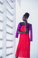 Attractive black woman wearing coral fringed dress walks the runway