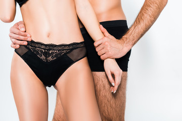 cropped view of couple in black underwear isolated on grey